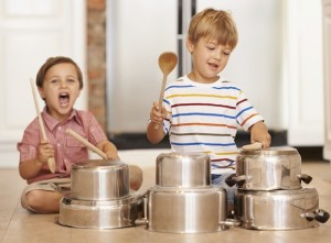 Two young brothers testing their musical skills on kitchen utensils
