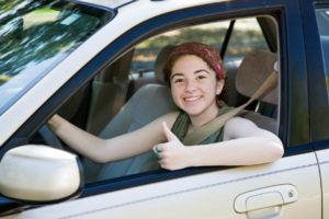 Cute teen driver giving the thumbs up after passing her driving test.
