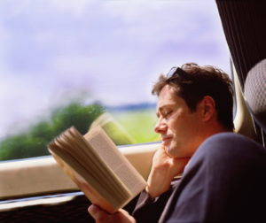 Young man travelling on train, reading book, profile