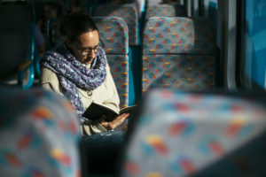 reading-woman-reading-book-on-train-bus